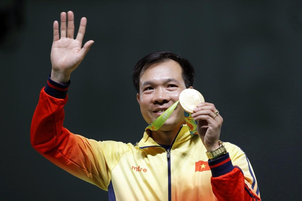 Hoang Xuan Vinh of Vietnam celebrates with his gold medal on the podium after winning the men's 10m